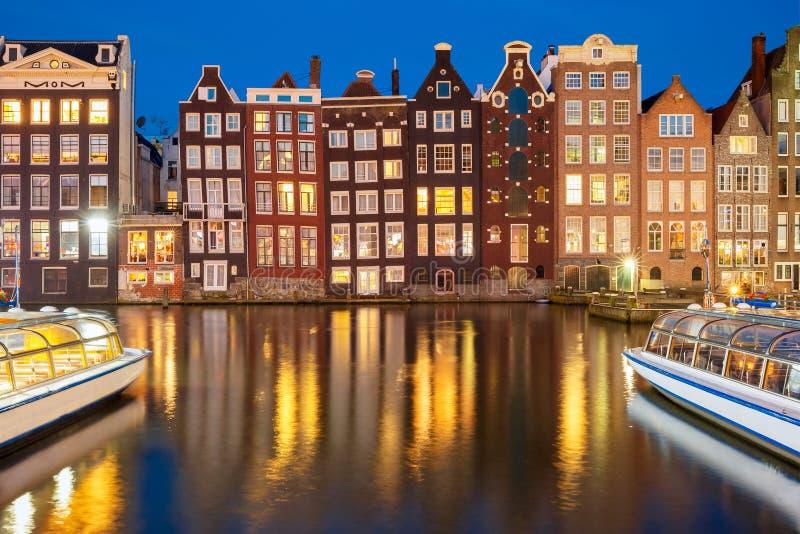 夜阿姆斯特丹运河的Damrak,荷兰,荷兰跳舞房子 库存图片