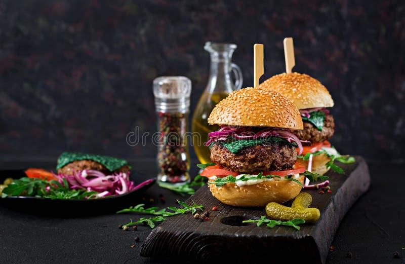 大三明治-汉堡包汉堡用牛肉,蕃茄,蓬蒿乳酪 库存照片