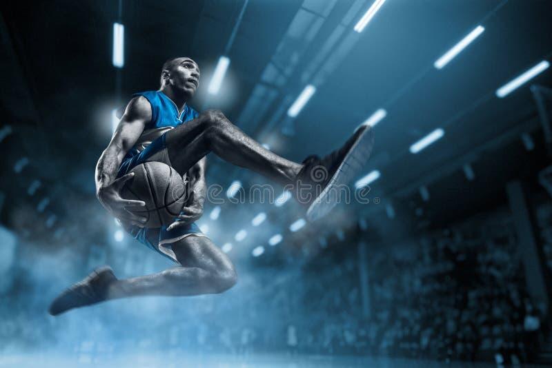 大专业竞技场的蓝球运动员在比赛期间 做灌篮的蓝球运动员 免版税库存照片