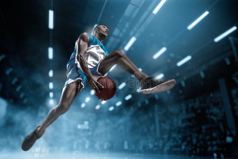 大专业竞技场的蓝球运动员在比赛期间 做灌篮的蓝球运动员 免版税库存图片