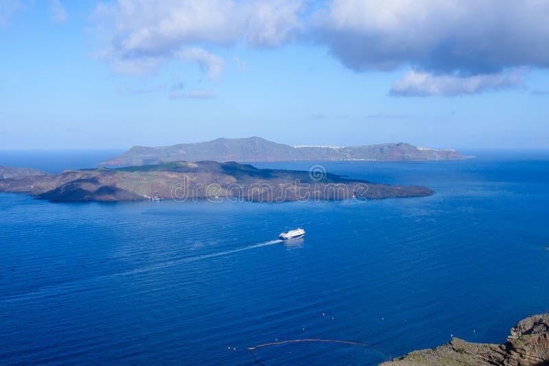 大乘客巡航划线员在离圣托里尼希腊海岛的海岸的附近  晴朗的温暖的早晨 巡航旅行 免版税库存照片