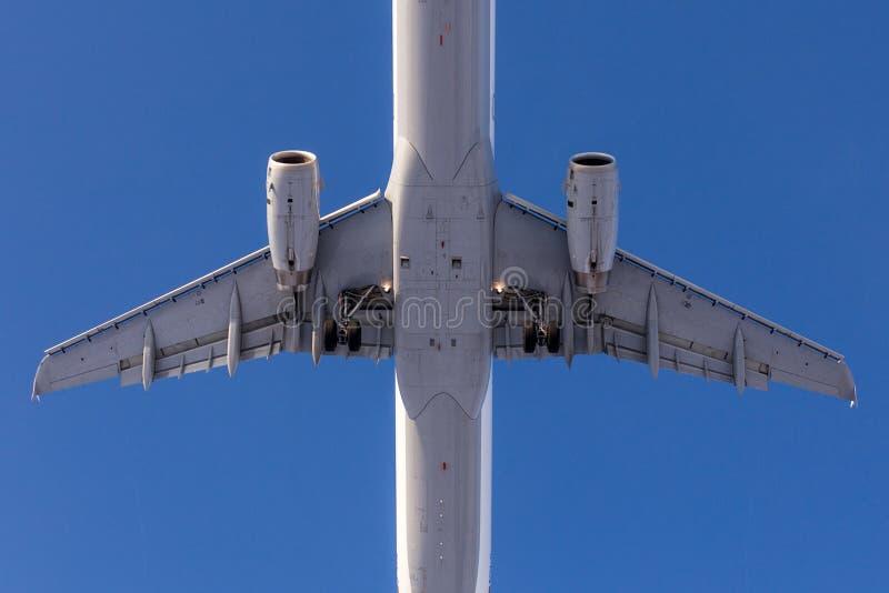 大乘客飞机特写镜头底视图  在背景的蓝色清楚的天空 免版税库存图片