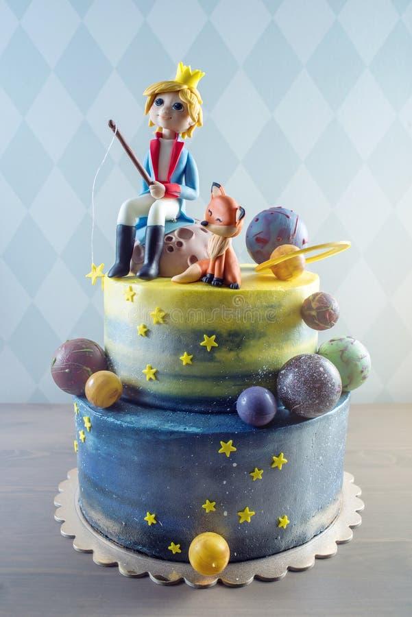 大以与小王子和Fox的乳香树脂小雕象的行星的形式装饰的孩子美丽的蛋糕 库存图片