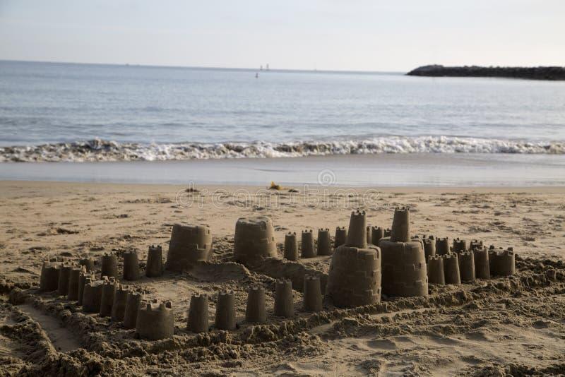 大儿童的在海滩小海浪的沙子城堡 库存照片