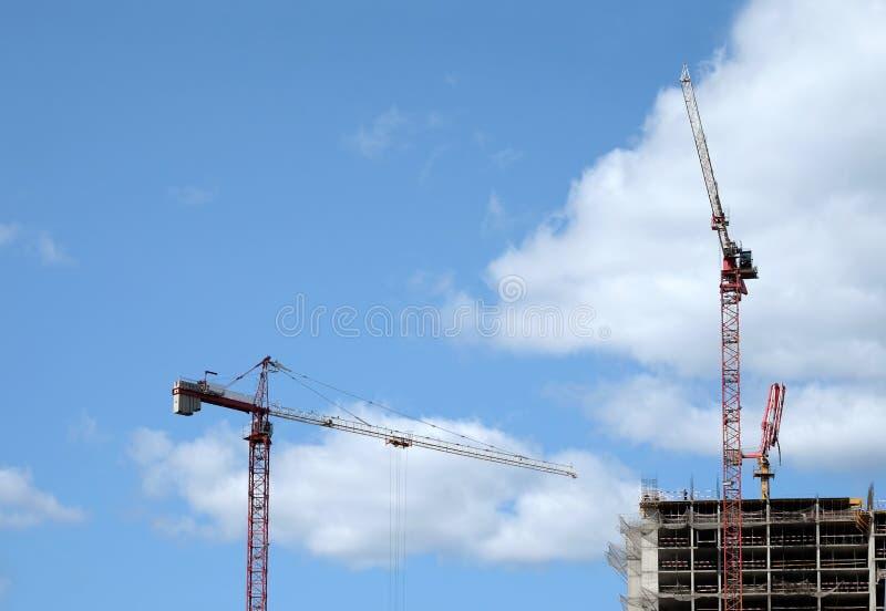 大卷扬的塔吊和现代建筑大厦的顶面部分在蓝天的一个城市与云彩 库存照片