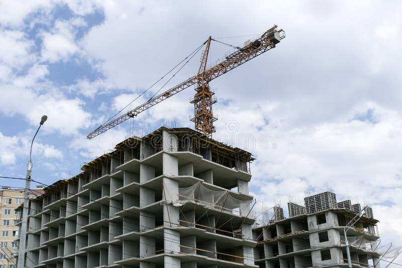 大厦具体框架和在他们上的一台建筑用起重机 库存照片