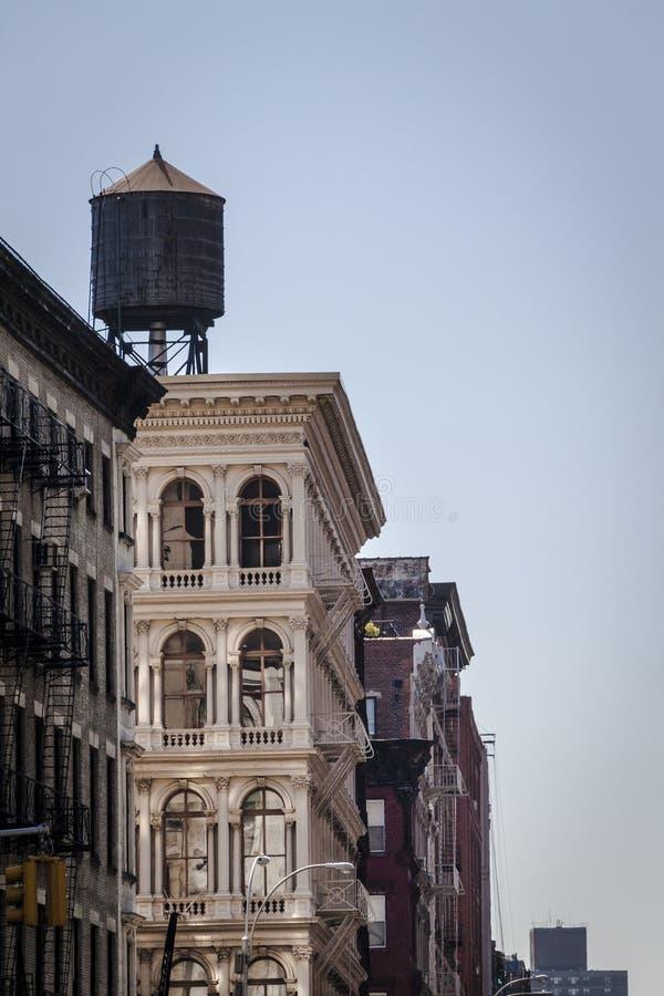 大厦和储水箱在老房子街市在纽约 库存照片