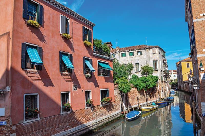 大厦和小船在一条运河前面在威尼斯 库存图片