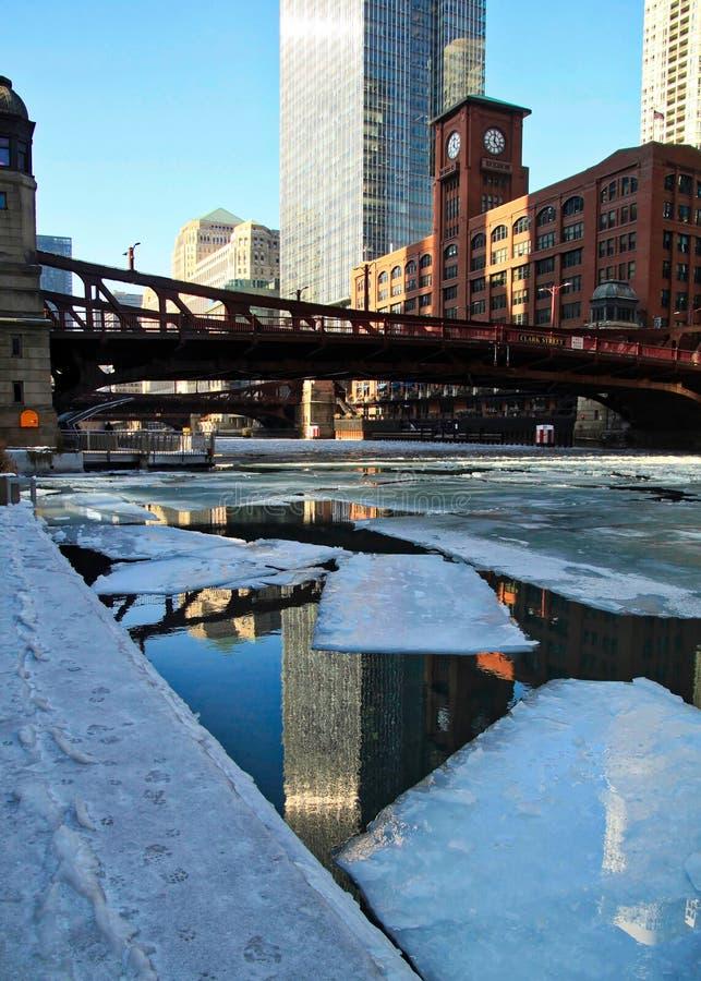 大厦的反射在水中,当桥梁跨过有冰大块的时冻芝加哥河 免版税库存照片