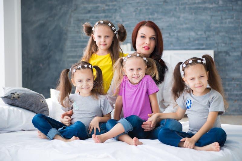 大友好的家庭,许多孩子:妈妈和四个相当快乐的女孩三倍孪生姐妹坐床反对灰色 库存图片