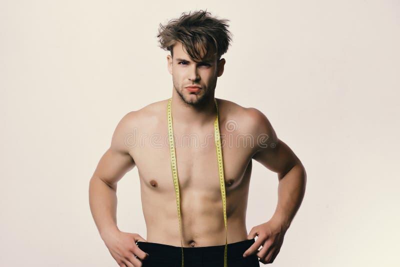 大号和黄色测量的磁带人举行黑牛仔裤  有杂乱头发和赤裸躯干的运动员 免版税库存图片
