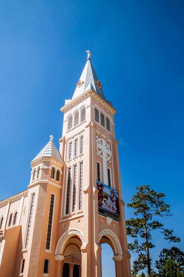 大叻市大教堂反对明亮的天空蔚蓝的黄色喇叭花塔 库存图片