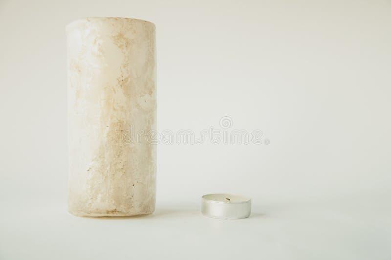 大和小白色蜡烛在桌上 免版税库存图片