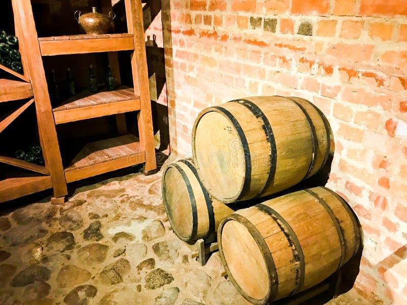 大啤酒的,酒回合木桶在中世纪的老地窖里由砖制成 库存照片