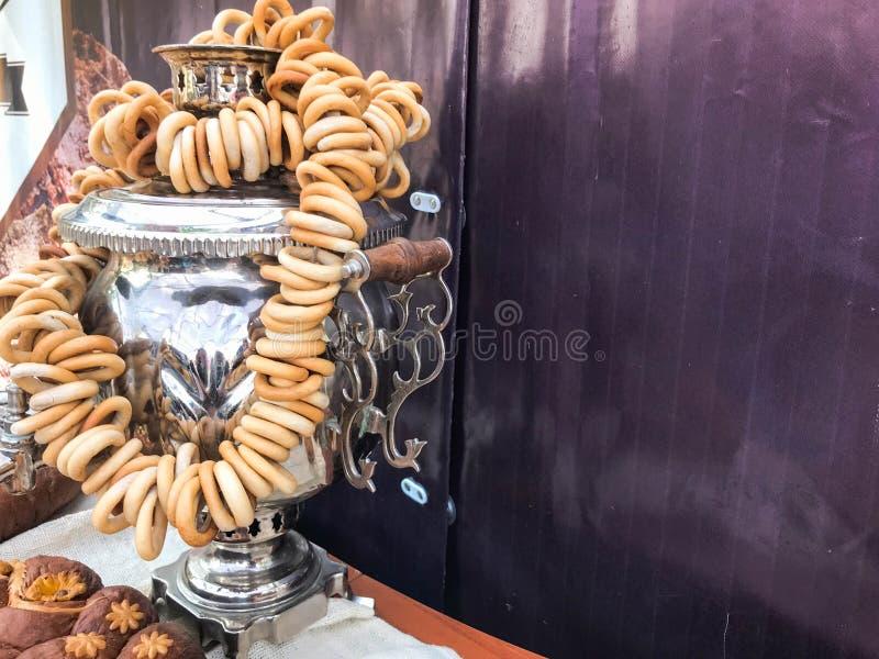 大喝的茶的,与一束的酿造茶金属银发光的老传统俄国俄国式茶炊sushiks,百吉卷,快餐 免版税库存图片