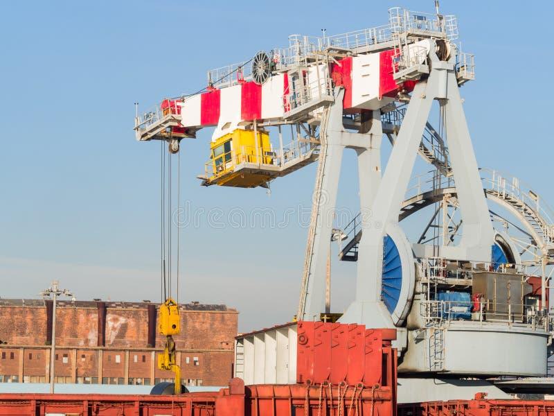 大在货船的口岸起重机装货钢卷 免版税库存图片