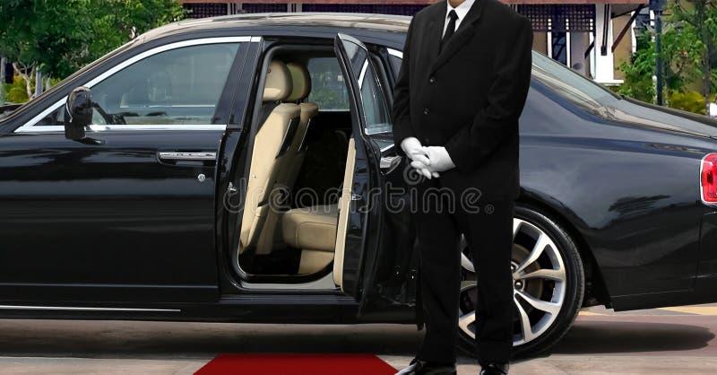 大型高级轿车在被打开的车门旁边的司机身分与隆重 免版税库存图片