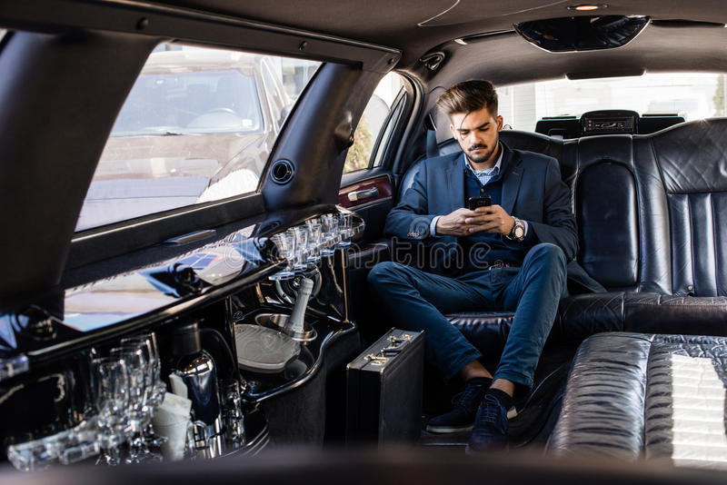 大型高级轿车的年轻商人键入在巧妙的电话的 库存图片