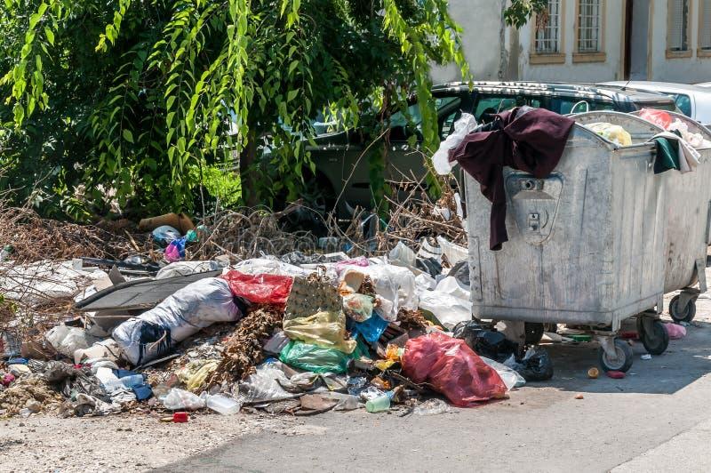 大堆在街道和破烂物倾销的溢出垃圾在大型垃圾桶附近在城市能 库存图片