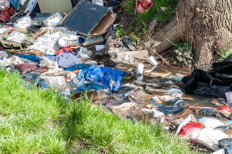 大堆垃圾和破烂物在污染自然与废弃物的河水 免版税库存图片