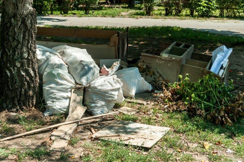 大堆或堆垃圾和破烂物在街道附近污染有气味和废弃物的草倾销了城市 库存照片