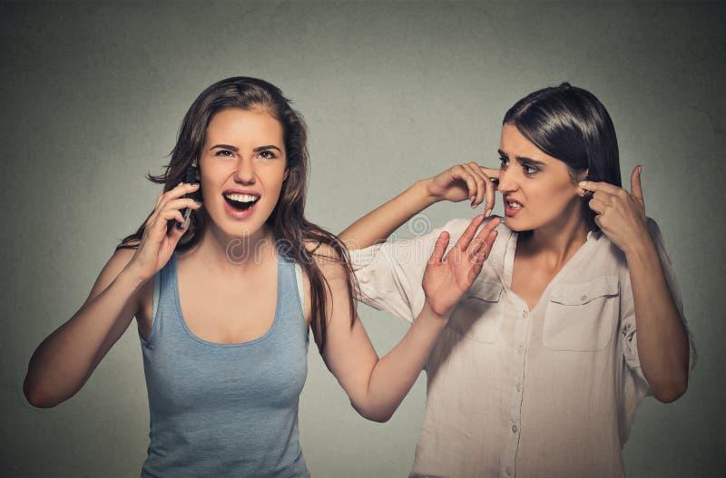 大声两名的妇女,讨厌粗鲁的妇女响亮地谈话在手机 图库摄影