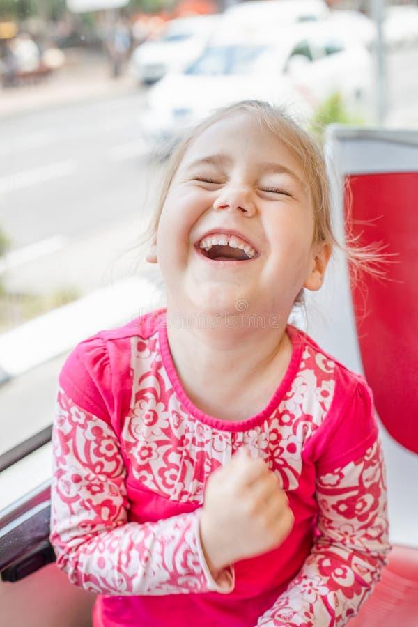 大声笑在公共汽车的滑稽的女孩 库存图片