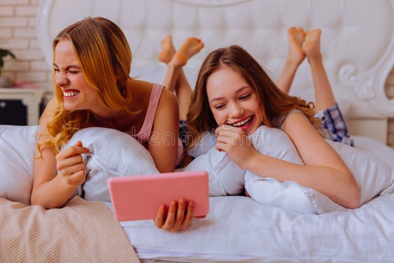 大声笑在观看的姐妹与兄弟姐妹的喜剧以后 免版税库存图片