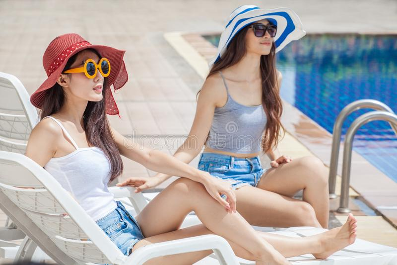 大夏天帽子和太阳镜的两名美丽的年轻亚裔妇女坐一起sunbed由游泳场 E 免版税库存照片