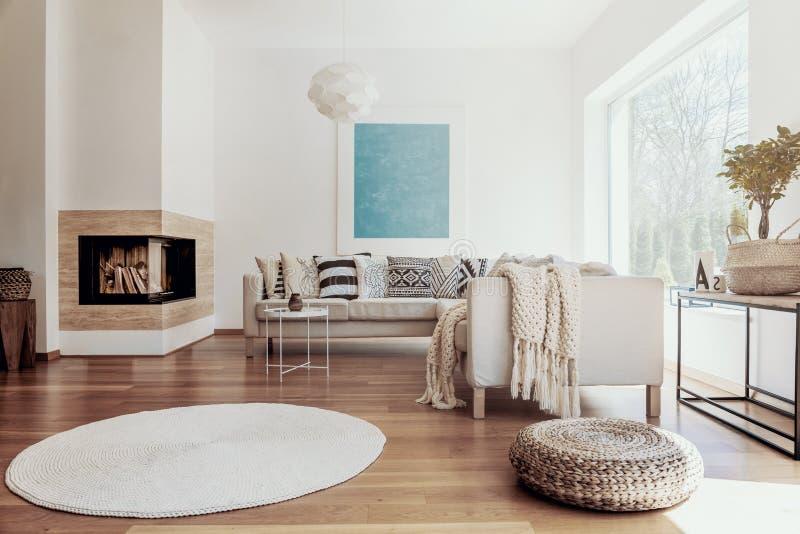 大天蓝色抽象派海报和一个现代壁炉在明亮的客厅内部与黑暗的硬木地板 库存图片