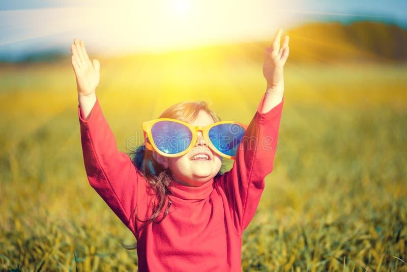 戴大太阳镜的小女孩看太阳 免版税图库摄影