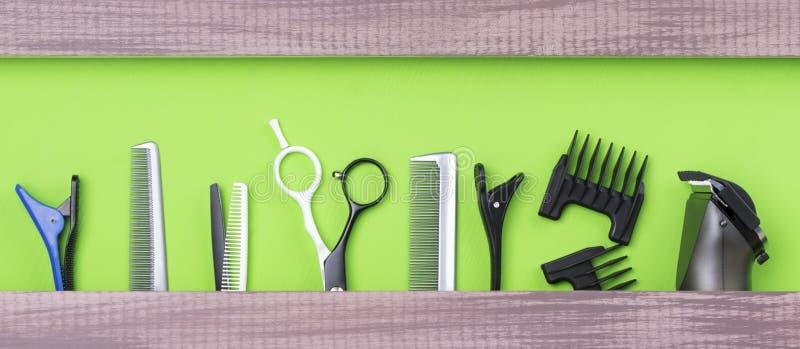 大套剪的头发美发师在绿色背景 免版税库存图片