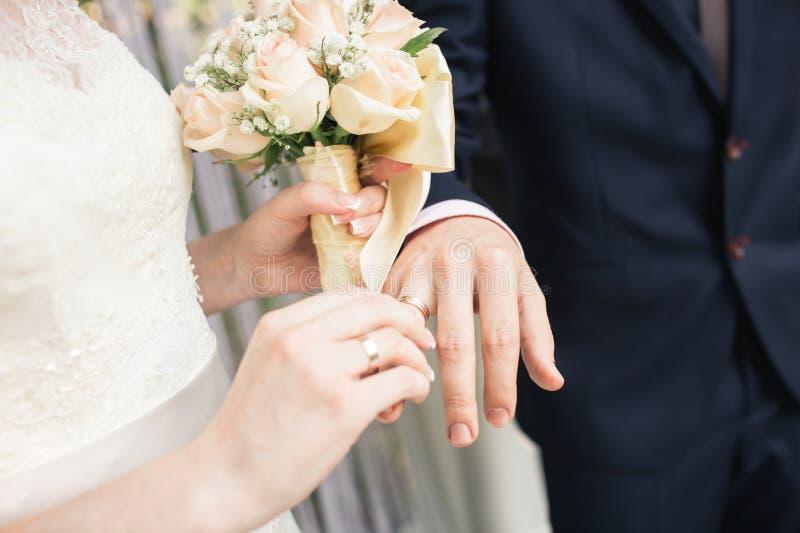 大好的婚礼花束在妇女` s手上 新娘在新郎` s手指上把圆环放 免版税库存照片