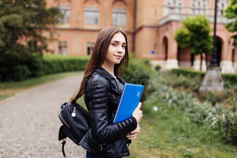 大学学院看起来愉快微笑与书或笔记本的学生女孩在校园公园 免版税库存照片
