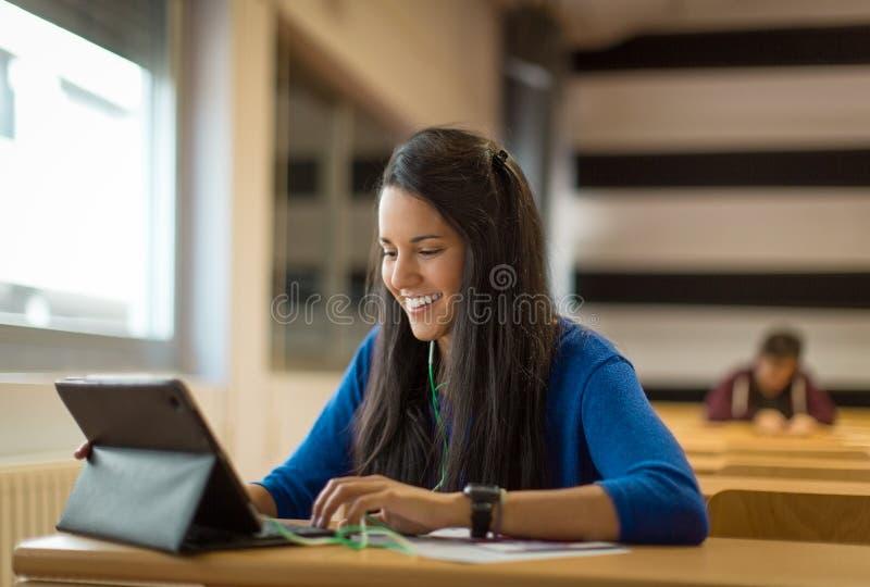 大学教室的微笑的年轻女学生 免版税库存图片