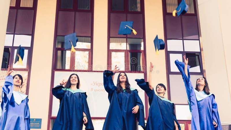 大学毕业生在天空中的投掷毕业帽子 小组学术礼服的愉快的毕业生在大学大厦附近 免版税库存照片
