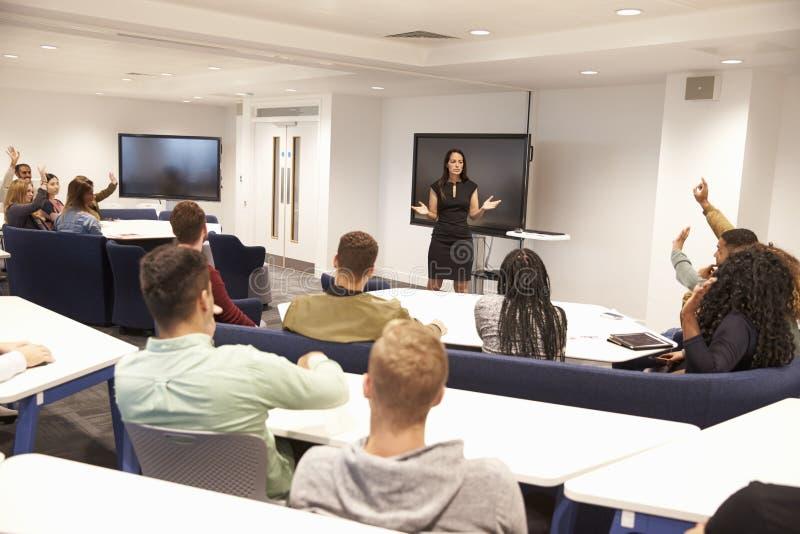 大学生在有女性讲师的教室学习 库存照片