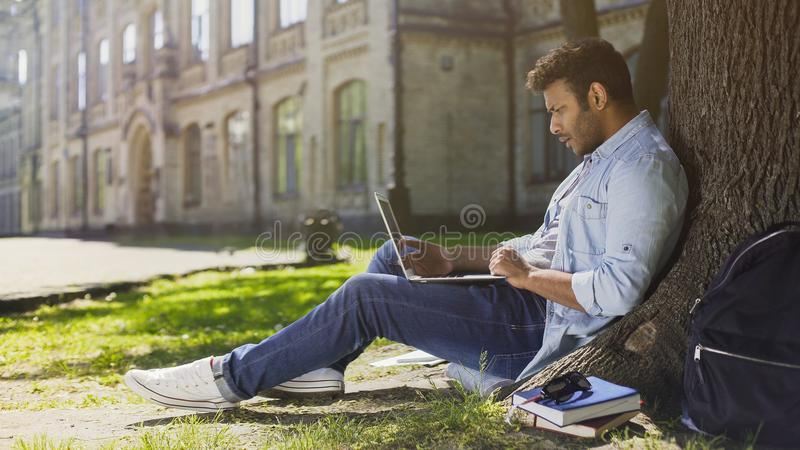 大学生在树下,使用看起来的膝上型计算机惊奇的,生气的新闻 免版税图库摄影