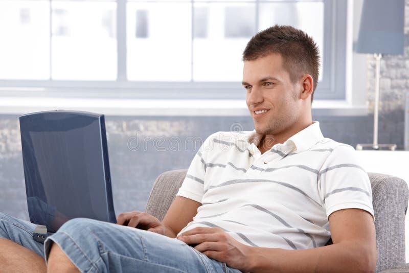 大学生微笑浏览的互联网在家 库存图片