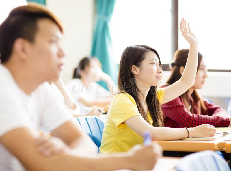 大学生问题的培养手在教室 免版税图库摄影
