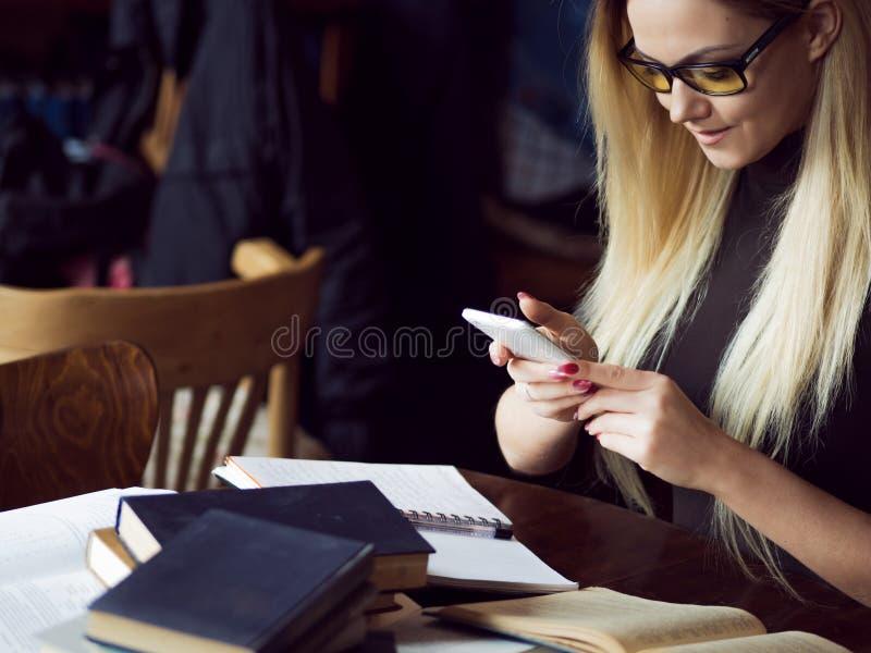 大学的少妇学生 准备检查和吸取教训在公立图书馆里 库存照片