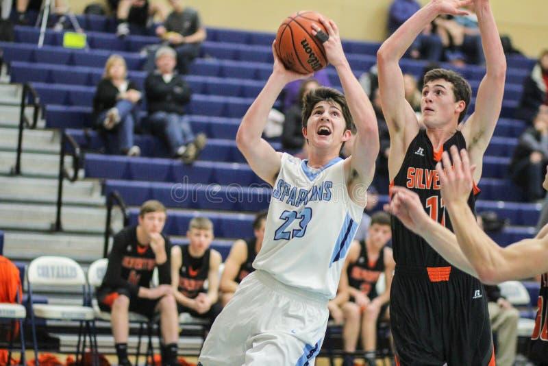 大学运动代表队高中蓝球运动员向篮子求助;守卫由对手 免版税库存照片
