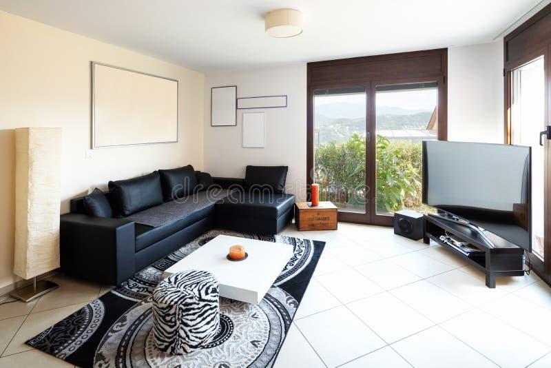 大客厅有大黑皮革沙发,大屏幕和意想不到的视图 库存照片