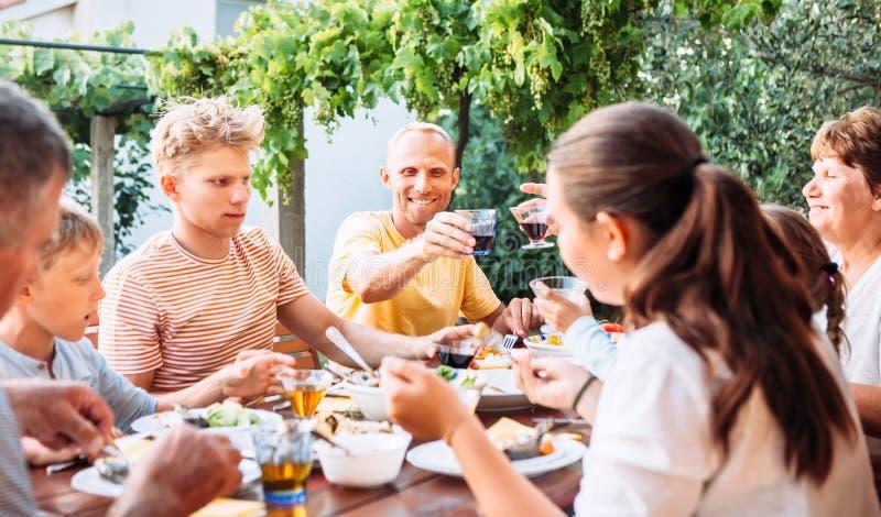 大家庭吃在露天的晚餐在夏天庭院 免版税库存照片