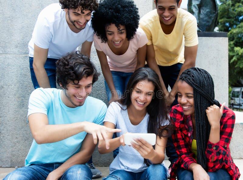 大小组与电话的年轻成人赌博 免版税库存照片