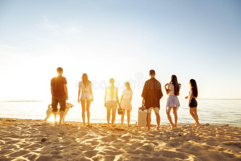 大小组朋友picknic日落的海滩 图库摄影