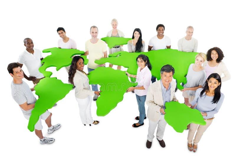大小组有世界地图的保守的人 库存图片