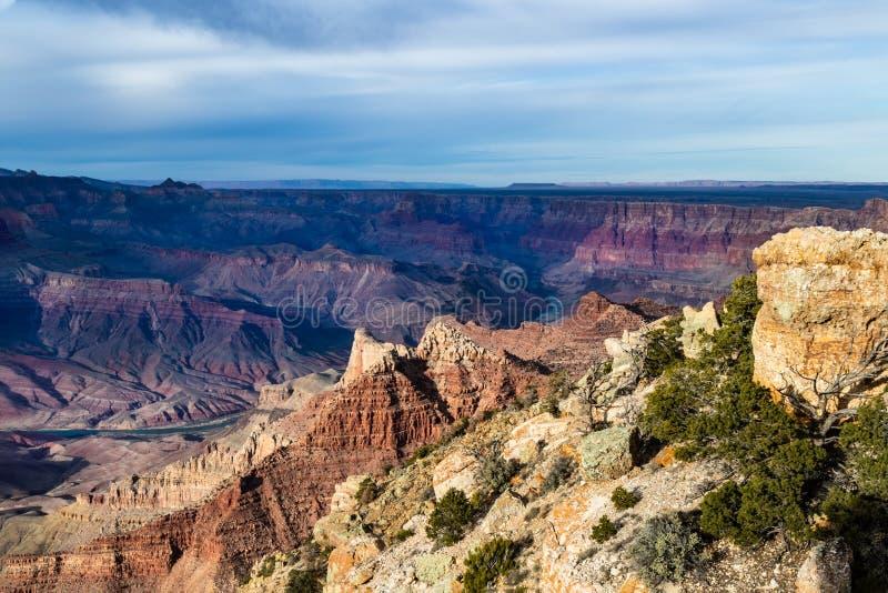 大峡谷,从Lipan点的看法 小山,在前景的岩石;以远峡谷、北部外缘和河 免版税图库摄影