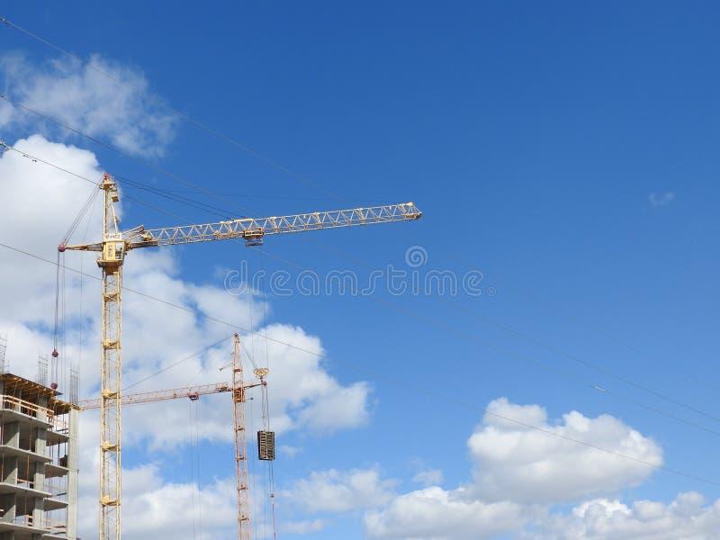 大工地工作,包括运转在建筑复合体的几台起重机,与一清楚的天空蔚蓝 库存照片