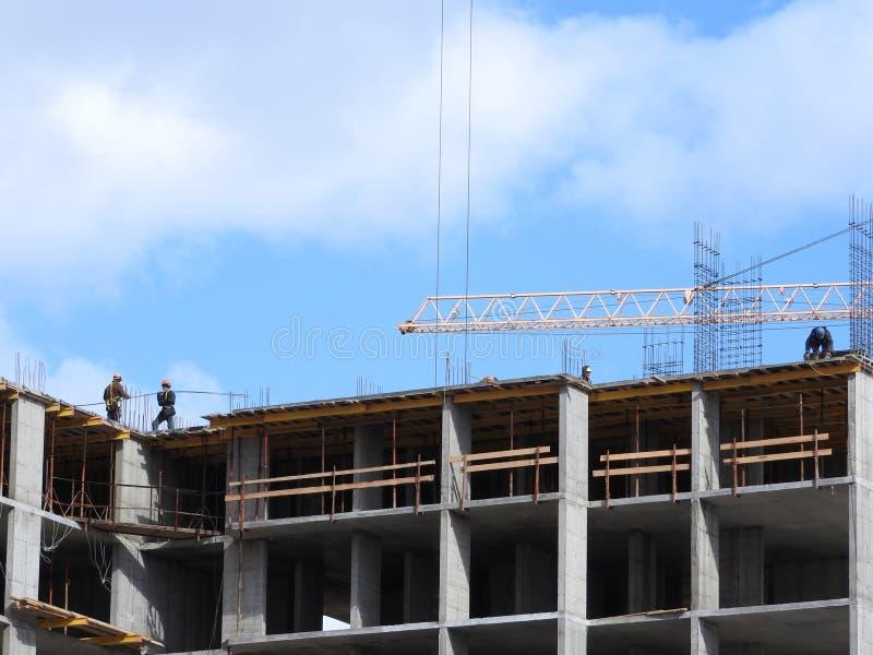 大工地工作,包括运转在建筑复合体的几台起重机,与一清楚的天空蔚蓝 免版税图库摄影